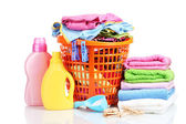 Clothes with detergent and washing powder in orange plastic basket isolated on white — Stock Photo