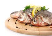 Frische fische mit zitrone, petersilie und gewürzen aus holz schneidebrett isoliert auf weiss — Stockfoto