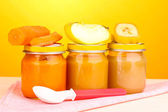Jars of baby puree with spoon on napkin on yellow background — Stock Photo
