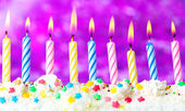 Beautiful birthday candles on purple background — Stock Photo