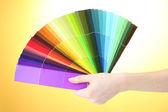 Hand met helder palet van kleuren op gele achtergrond — Stockfoto