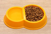 Dry cat food and water in yellow bowl on wooden background — Stock Photo