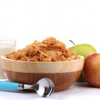 Tasty cornflakes in wooden bowl, apples and glass of milk isolated on white — Stock Photo #9702874