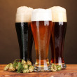 Three glasses with different beers and hop on wooden table on brown background — Stock Photo