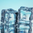 Melting ice cubes on blue background — Stock Photo
