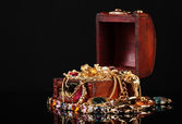 Wooden chest full of gold jewelry on black background — Stock Photo