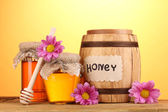 Sweet honey in barrel and jars with drizzler on wooden table on yellow background — Stockfoto