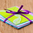 Bunch of color envelopes with ribbon on wooden background — ストック写真