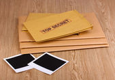 Envelopes with top secret stamp with photo papers on wooden background — Stock Photo