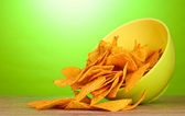 Tasty potato chips in green bowl on wooden table on green background — Stock Photo