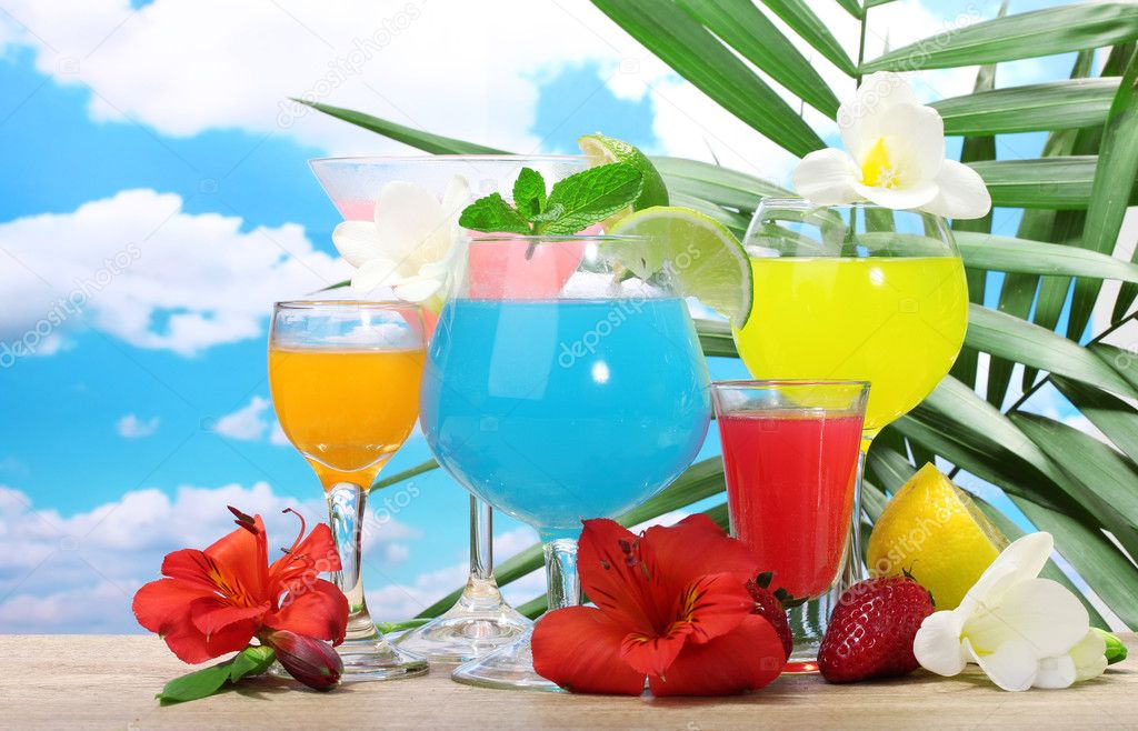 Exotic cocktails and flowers on table on blue sky background — Stock Photo #9722173