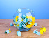 Pieces of paper for lottery in vase on wooden table on blue background — Stock Photo