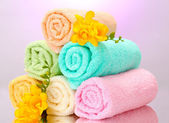 Colorful towels and flowers on purple background — Zdjęcie stockowe