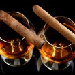Stock Photo: Two glasses of brandy and cigars on black background