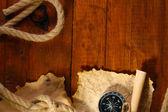 Papel velho, bússola e corda sobre uma mesa de madeira — Fotografia Stock