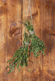 Fresh green thyme hanging on rope on wooden background — Stock Photo