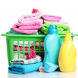 Detergents and towels in green plastic basket isolated on white — Stock Photo