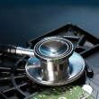 Stethoscope on hard disk drive on dark blue background — Stock Photo
