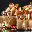 Various gold jewellery and gifts on black background — Stockfoto