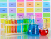 Test-tubes and flasks with color liquid on color samples background — Stock Photo