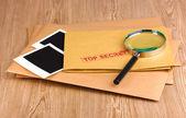 Buste con timbro segreto superiore con carta fotografica e lente di ingrandimento su fondo in legno — Foto Stock