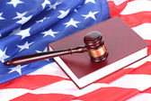 Mazo de juez y libro sobre fondo de bandera americana — Foto de Stock