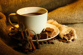Cup of coffee and beans, cinnamon sticks and chocolate on sacking background — Stock Photo