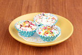 Creamy cupcakes on saucer on wooden background — Stock Photo