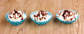 Creamy cupcakes on wooden background — Stock Photo