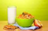 Tasty cornflakes in green bowl, apple and glass of milk on wooden table on green background — Stock Photo