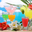 Royalty-Free Stock Photo: Exotic cocktails and flowers on table on blue sky background