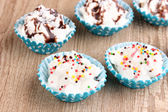 Creamy cupcakes on wooden background close-up — Stock Photo