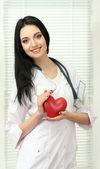 Mladá krásná doktor s stetoskop drží srdce — Stock fotografie