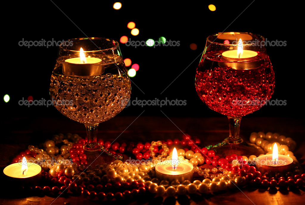Amazing composition of candles and glasses on wooden table on bright background  Stock Photo #9798783