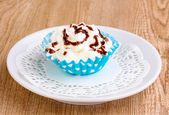 Creamy cupcake on saucer on wooden background — Stock Photo