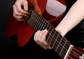 Guitar in hands isolated on black — Stock Photo