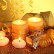 Beautiful candles, gifts and decor on wooden table on yellow background - Zdjęcie stockowe