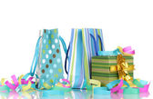 Colorful gift bags and gifts with serpentine isolated on white — Stock Photo