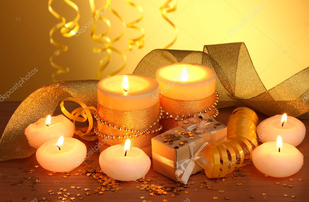 Beautiful candles, gifts and decor on wooden table on yellow background — Stock Photo #9837390