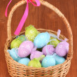 Colorful easter eggs in basket on wooden background — Stock Photo