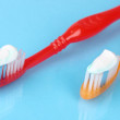 Toothbrushes with paste on blue background — Stock Photo