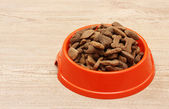 Dry dog food in orange bowl on wooden background — Stock Photo