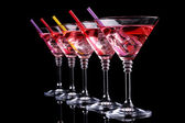 Red cocktail in martini glasses isolated on black — Stock Photo
