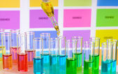 Test-tubes with color liquid and pipette on color samples background — Stock Photo