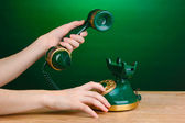 Dialing on retro phone on wooden table on green background — Stock Photo