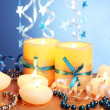 Stock Photo: Beautiful candles, gifts and decor on wooden table on blue background