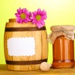 Sweet honey in jar and barrel with drizzler on wooden table on green background — Stock Photo