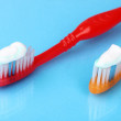 Stock Photo: Toothbrushes with paste on blue background