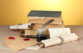 Old books, scrolls, feather pen and inkwell on wooden table on yellow background — Stock Photo