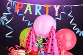 Party items on purple background — Stock Photo
